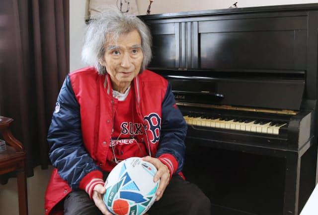 中学時代に父・開作さんがライカのカメラを手放して購入したピアノの前で。ゴム素材の楕円球を手に「革のボールが見たいよ」