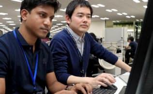インド出身のアトゥル・ゴタムさん(左)の仕事ぶりは周囲に刺激を与える(コニカミノルタの開発拠点、東京都八王子市)