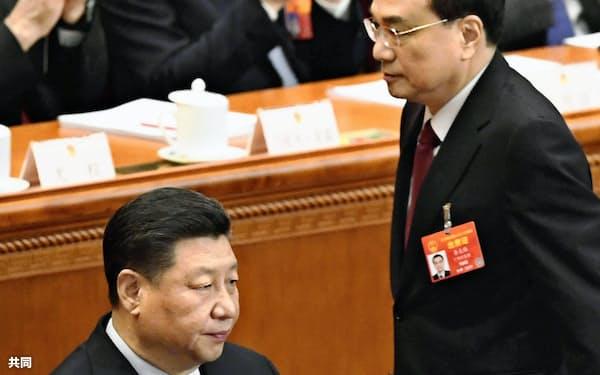 開幕した中国全人代で、政府活動報告のため席を立つ李克強首相。左は習近平国家主席(5日、北京の人民大会堂)=共同