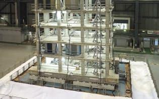 振動実験の模様。よく見ると試験体が変形して1階床の右側が持ち上がっている(写真:池谷和浩)