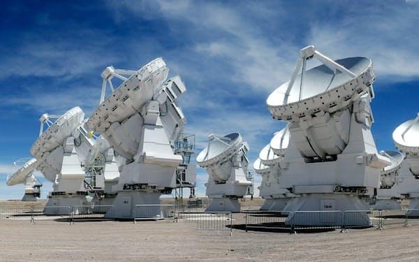 チリ、アンデス山脈の海抜5000mに並ぶ「アルマ」望遠鏡。右端が取材中の筆者(写真・日経BPコンサルティング)