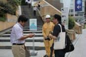 通行できない設定となった六本木ヒルズの階段前でスマートフォンで情報収集する参加者