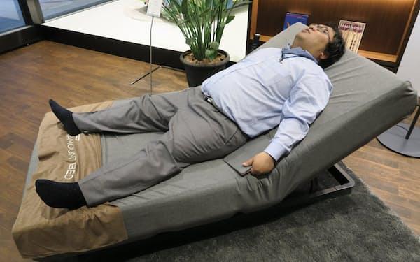 睡眠の状態に合わせて変形する電動ベッド。M記者はメモを取るためのiPadを抱えたまま、既に寝落ちするかに見えた(撮影:日経 xTECH)