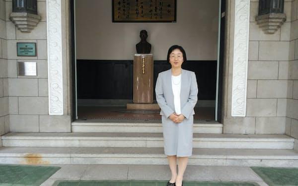 広島大学付属中学・高校の鈴木由美子校長。後ろは原爆の被害を受けながら倒壊を免れた講堂