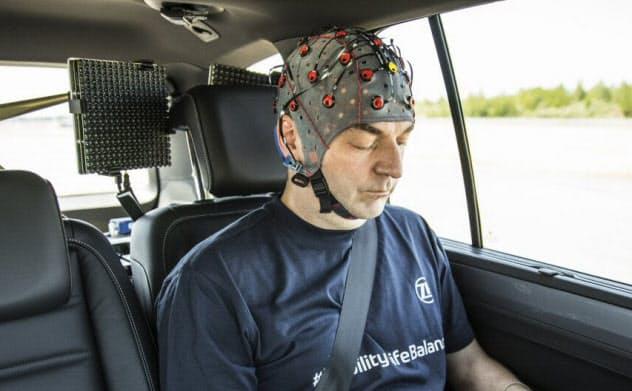 車酔いに関する実験の様子。被験者は脳波計などを装着し、タブレット端末上で特定の作業をする(出所:ZF)