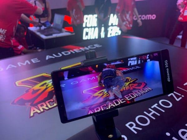 NTTドコモのブースで実施したARを使った対戦ゲームの観戦デモ。目の前の机の上にスマホをかざすと、格闘ゲームのキャラクターが出現し、机の上で戦いを繰り広げる(撮影:日経 xTECH)