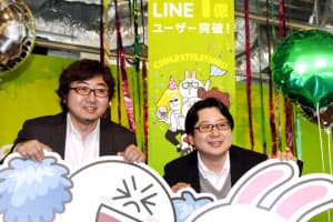 「LINE」の利用者数1億人突破で笑みを見せるNHN Japanの森川亮社長(左)と舛田淳執行役員(18日、東京都渋谷区)
