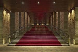 写真2 れんがと赤じゅうたんで出迎えるフェスティバルホールの入り口にある大階段。赤じゅうたんとLEDを用いた照明で音楽ホールの非日常的な空間を演出する(写真:生田将人)