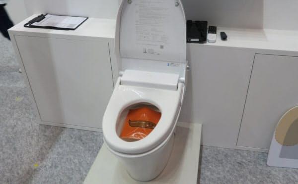 便観察機能を備えたトイレ。写真ではケースに入っているが、実際にはケースからリアルな模型を出してデモを行っている(撮影:日経 xTECH)