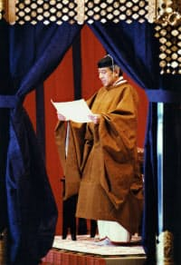 平成時の即位礼正殿の儀。在位当時の上皇さまが身を包んでいるのが黄櫨染御袍(こうろぜんのごほう)と呼ばれる装束(1990年11月)=共同