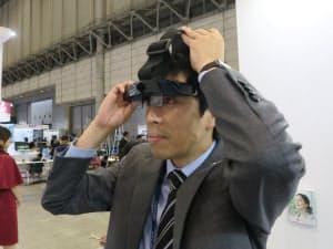 「両眼軽量ARグラス」。写真では手で押さえているが、実際には頭にバンドで固定する(撮影:日経 xTECH)