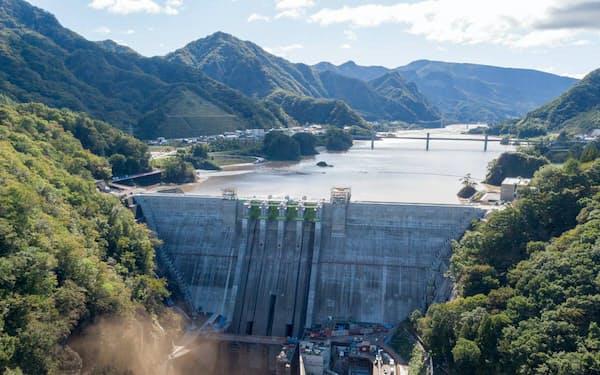 台風19号が通過した後の10月13日午後2時に撮影した八ツ場ダム。利水放流管から泥混じりの水が噴き出し、土煙を上げる。許可が不要なダム下流の吾妻峡からドローンを離着陸させて撮影した