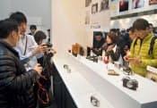 デジタルカメラの展示会「CP+2013」のオリンパスのブースで小型デジカメを見る来場者(1月31日、横浜市)