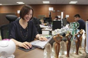 サイバー子会社、パシャオクの石田裕子社長。デスクには広告営業時代の社内表彰のトロフィーが並ぶ