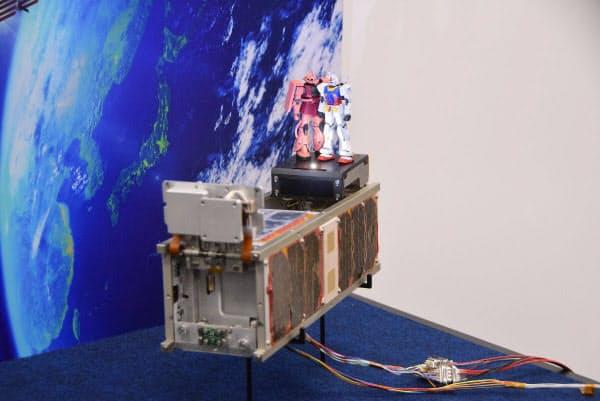 ガンダムとシャアザクのガンプラを搭載した超小型衛星「G-SATELLITE」のエンジニアモデル。秒速8kmで地球周回軌道を飛行しながら、東京2020大会へ応援メッセージを発信する(写真:久我智也)