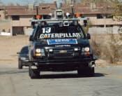 図2  開発競争が起こるきっかけになった、米国防総省の研究機関(DARPA)が主催した「Urban Challeng」。市街地を模擬したコースで無人の車両を走らせた。写真は優勝したカーネギーメロン大学とGMなどが共同で開発した車両。人が乗らないので、フロントガラスに字が大きく書いてある