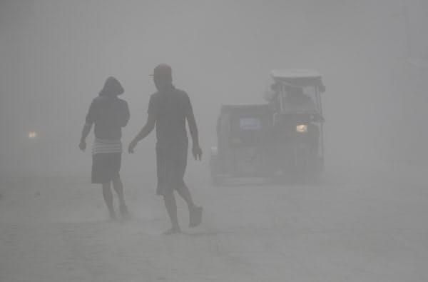 タール火山の噴火による降灰が広がる中で歩く住民=AP