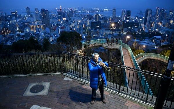 神戸の市街地を望む諏訪山公園で、追悼の思いを込めトランペットを吹く松平晃さん(17日午前、神戸市中央区)=笹津敏暉撮影