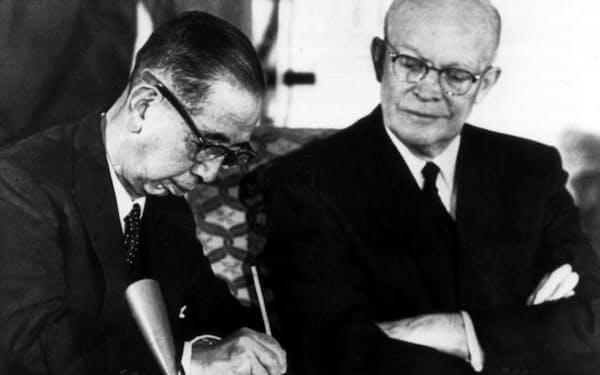 日米安保条約に調印する岸信介首相。右はアイゼンハワー米大統領。