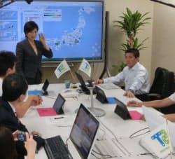 チームが用いる専用の部屋で、取り組みを解説する小池百合子衆議院議員(中央左側)と平井卓也衆議院議員(中央右側)