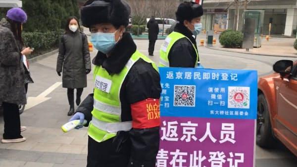 「社区」の入り口で通行人をチェックする人(北京市)