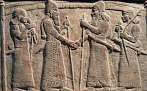 紀元前9世紀、バビロニア人と握手をするアッシリア王シャルマネセル3世をかたどったレリーフ。握手は古代の美術品にたびたび登場するモチーフだ(PHOTOGRAPH BY DEAGOSTINI, GETTY)