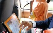 移動中の選挙カーでフェイスブックなどの書き込みをする候補者(7月4日、東京都内)