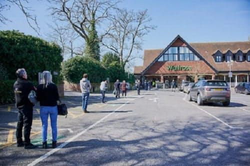 24日の英オックスフォードシャー州にあるスーパーマーケット「ウェイトローズ」。入場制限のため店の外で間隔を空けて順番を待つのが定着しつつある(写真:永川智子)