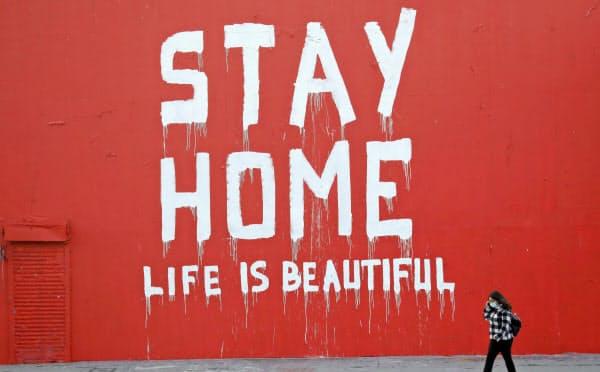 日本の緊急事態宣言の発令期間は5月6日までで、外出自粛の生活は少なくとも約1カ月間に及ぶ(「家にいよう」と壁に書いて呼びかけているロサンゼルスの風景)=AP