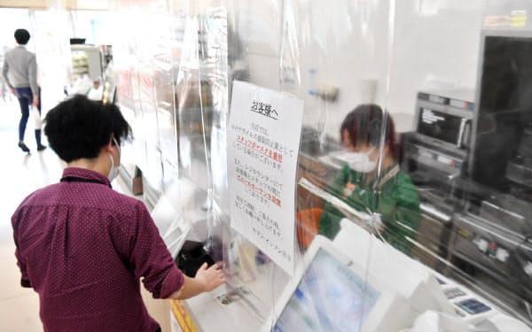 透明な仕切り越しに接客するコンビニエンスストアの従業員(東京都港区)=野岡香里那撮影