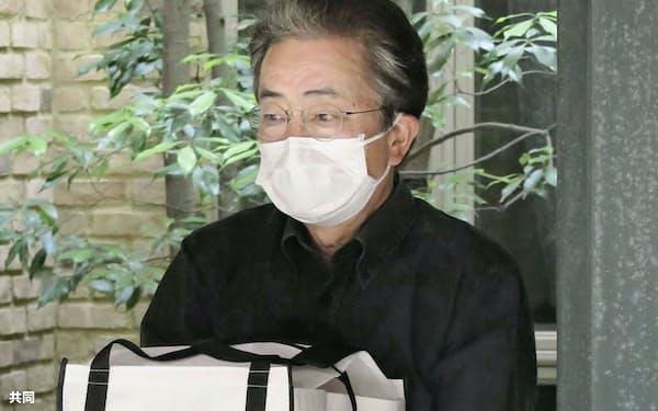 亡くなった岡江久美子さんの遺骨を抱える夫の大和田獏さん(24日夕)=共同