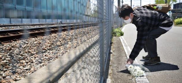脱線事故現場近くで花束を手向ける男性。高校の同級生を亡くし、毎年訪れている(25日、兵庫県尼崎市)