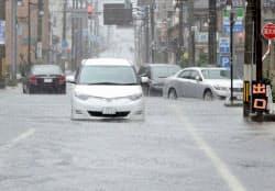 大雨特別警報が出された福井県小浜市の冠水した道路で立ち往生する車(16日午前8時30分ごろ)=共同