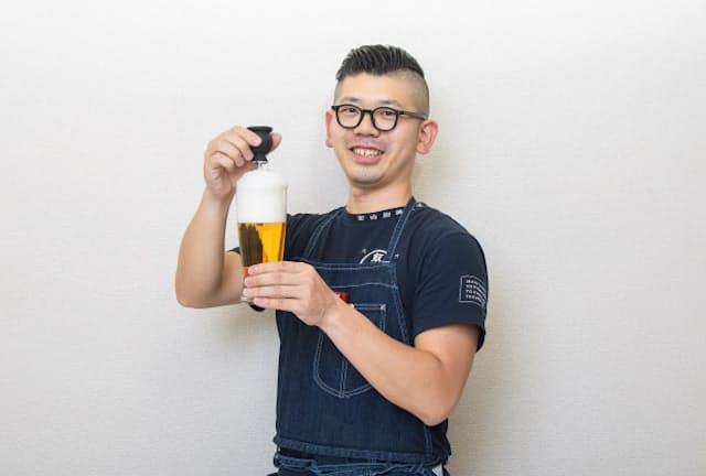 台所番長こと、合羽橋の老舗料理道具店、飯田屋の6代目、飯田結太氏。手にしているのは、缶から注いだビールの泡がクリーミーな泡に変わる「アエロメイト」