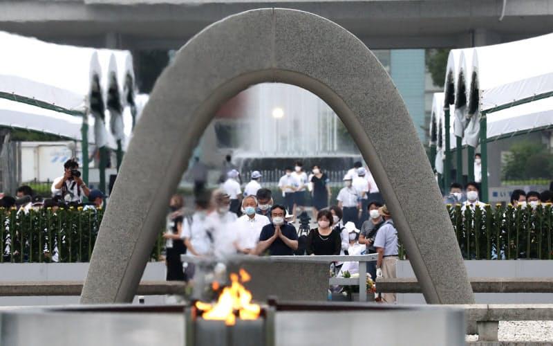 原爆慰霊碑に向かい犠牲者の冥福を祈る人たち(6日午前、広島市中区の平和記念公園)