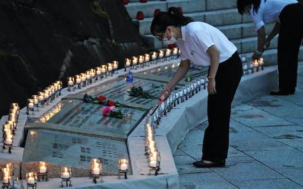 犠牲者の冥福を祈り、ろうそくをともす群馬県上野村役場の職員ら(12日)=藤井凱撮影