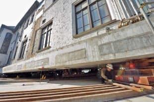 写真の左手前に向かって動く旧館。床下では作業員が建物を支える「ころ棒」の盛り替えや微調整などに追われる