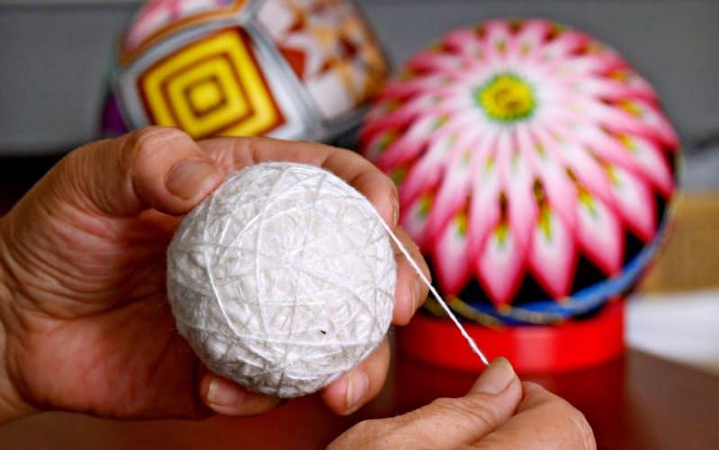 左手で綿の塊を回しながら右手で糸を巻きつけ、きれいな球を作る=笹津敏暉撮影