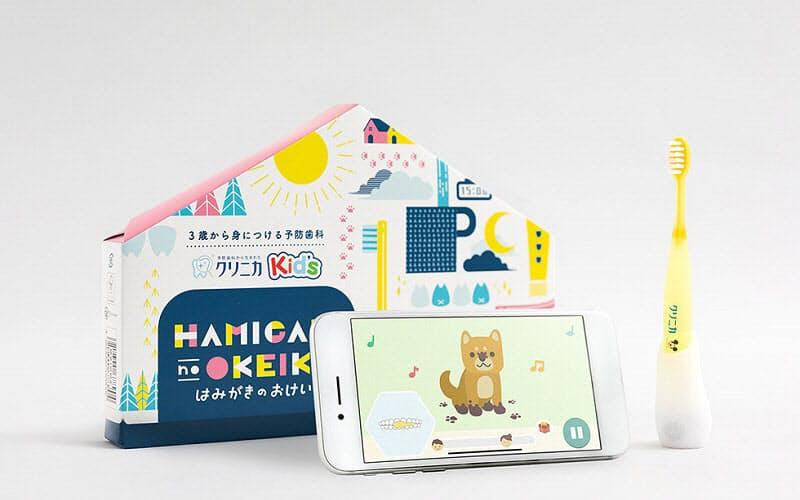ライオンが数量限定発売するIoTデバイスセット「クリニカKid's はみがきのおけいこ」。子供が喜ぶよう、専用の配送パッケージも用意した(写真後ろ側)