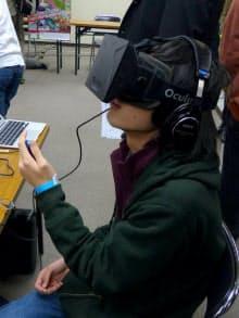 東京ロケテゲームショウで「木造校舎を歩く」をプレー中の参加者。左手に持ったコントローラーを操作して校舎の中を移動する