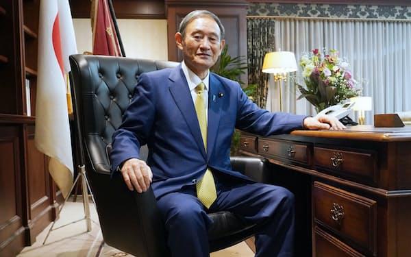 自民党の総裁に就任し、総裁の椅子に座る菅義偉官房長官(14日)