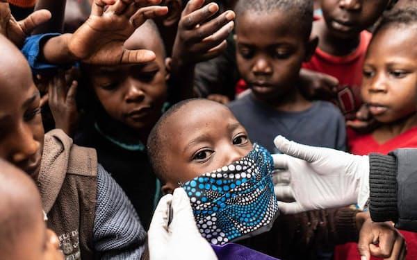 ケニア、ナイロビの恵まれない家族に食事を配る援助隊員が、男の子の顔にマスクを当ててみせる。新型コロナウイルスのパンデミックが経済危機を引き起こし、世界中の低所得層にしわ寄せが及んでいる(PHOTOGRAPH BY FREDRIK LERNERYD, AFP/GETTY)