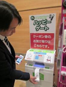 自販機の「クーポン獲得!」の画面を撮影したスマホを専用端末に持ち込むと、紙のクーポンが発行され売り場で使える(イオン幕張新都心店)
