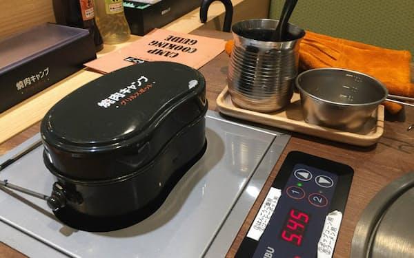 「焼肉キャンプ」名物の「キャンプ de 飯盒ご飯」。生米と水を入れた飯ごうがベルトコンベアでテーブルに運ばれる。ふつふつとご飯が炊き上がる音とにおいで、キャンプ気分が一気に盛り上がる