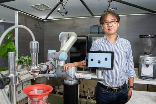 QBITロボティクス社長の中野浩也氏と、社内に展示したカフェロボット