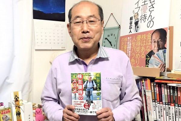 新刊本『桐谷さんの株主優待のススメ』を手にする桐谷さん