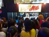 東京ゲームショウでの人気実況者のコーナー。中をのぞき込んでいるのはすべて女性だ(13年9月)