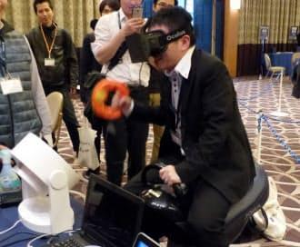 「オキュラス・リフト DK1」を利用した乗馬デモの様子。ユーザーが座っている「ジョーバ」が上下に振動し、右手で振っているのが鞭の役目をするセンサー。前方の白い物体は顔に向けて風を送る扇風機
