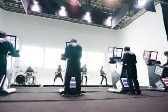 コナミデジタルエンタテインメントがアーケードゲーム機のPRでダンスロックバンド「HaKU(ハク)」と組んだ。写真はミュージックビデオの撮影風景