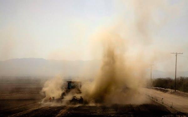 米カリフォルニア州サーマルで、農地を耕作するトラクター。耕作から発生する粉塵のせいもあって、この地域の大気の質は、連邦政府と州政府の基準を満たしていない。サーマルの町があるリバーサイド郡は、喘息による子どもの入院率がカリフォルニア州で最も高い(PHOTOGRAPH BY DAVID BACON, REPORT DIGITAL-REA/REDUX)